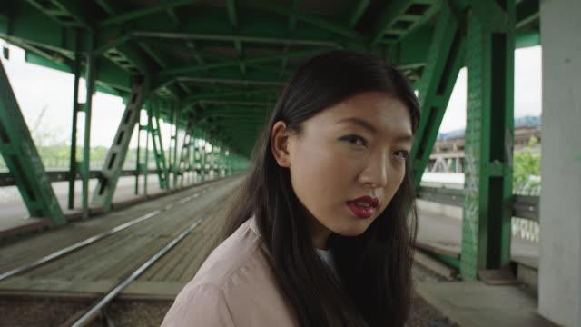 Young woman walking under bridge. Loneliness video