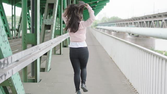 Young woman walking under bridge video