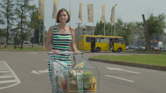 Young woman walking with full shopping cart on car parking near shopping center. Lady with grocery cart full of food and drink. Slow motion, steadicam shot. Young woman walking with full shopping cart on car parking near shopping center. Lady with grocery cart full of food and drink. Slow motion, steadicam shot. High quality 4k footage woman pushing cart stock videos & royalty-free footage