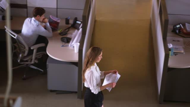 vídeos y material grabado en eventos de stock de mujer joven caminando con el papeleo en la oficina, elevada vista - cube