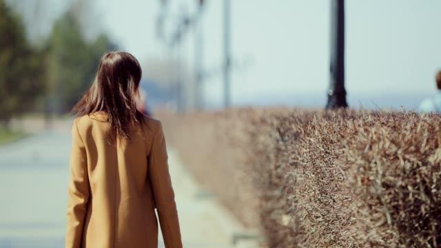 young woman walks down the street in spring. girl in a coat walks in the park. back view. - brązowe włosy filmów i materiałów b-roll