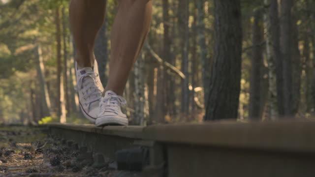 A young woman walks on old railway tracks.