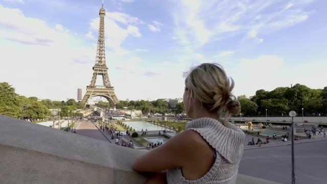 vídeos de stock, filmes e b-roll de jovem mulher vagando em paris perto da torre eiffel, frança - moda parisiense