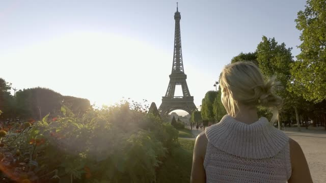 young woman wandering in paris near the eiffel tower, france - paris fashion stock videos and b-roll footage