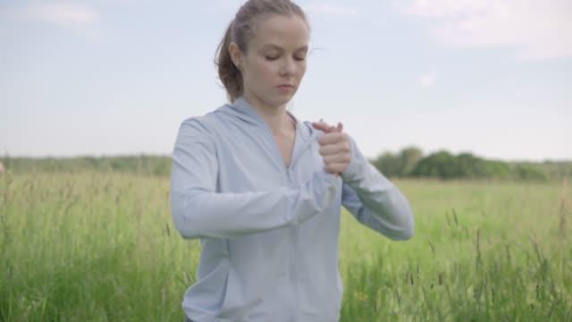 junge frau aufwärmen vor dem training. sportliche frau macht dehnübungen für die hände im freien - menschliches gelenk stock-videos und b-roll-filmmaterial