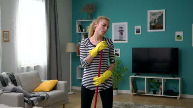 Young woman washes floor in apartment and sings a song in mop like a microphone video