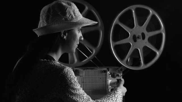 Young woman watching movie in old fashioned style film projector video