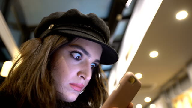 젊은 여자 스마트폰 충격에서에 보고 - surprise 스톡 비디오 및 b-롤 화면