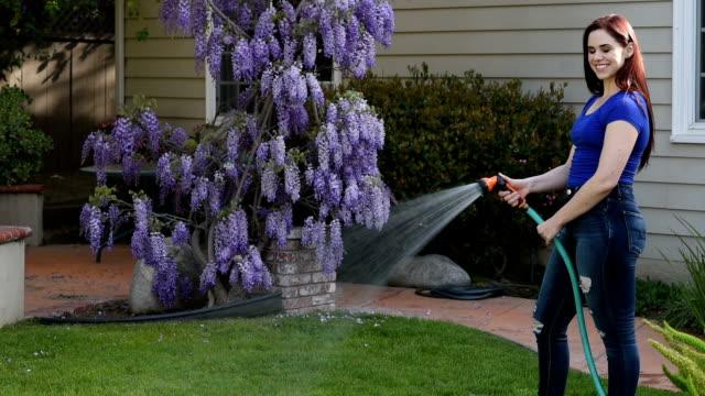 Jeune femme arrose son jardin - Vidéo