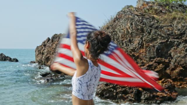 Junge Frau trägt einen Bikini tanzen mit der Flagge der Vereinigten Staaten am Strand. – Video