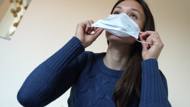 Young woman wearing a face mask during Coronavirus at home video