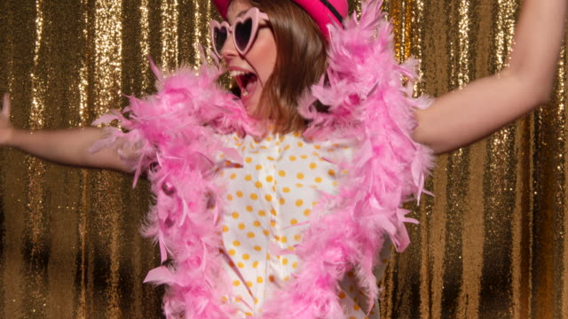 Young woman wearing a fun hat and glasses while posing for photos in the photo booth