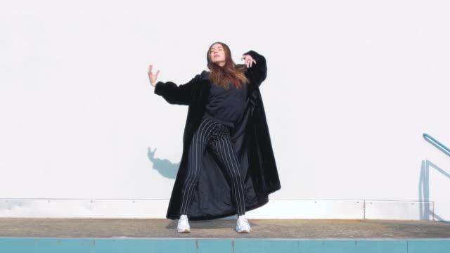 Young Woman Wearing a Large Black Winter Coat Dancing