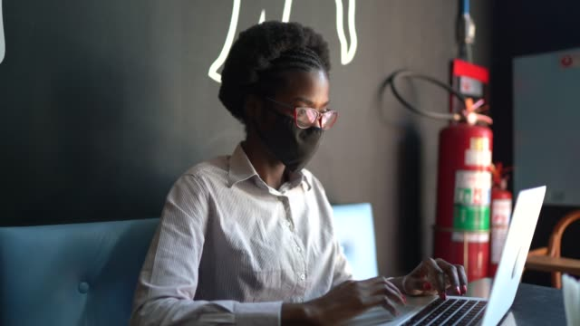 vídeos de stock e filmes b-roll de young woman wearing a protective face mask and using a laptop in a restaurant - afro latino mask