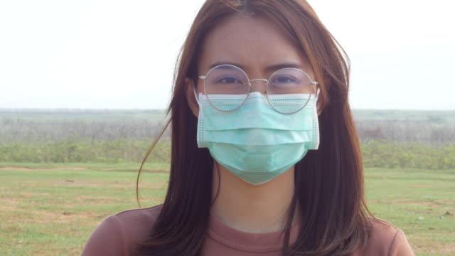 Ung kvinna bär en skyddande ansiktsmask headshot video