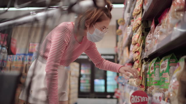 Young woman wearing a protective face mask shopping in supermarket