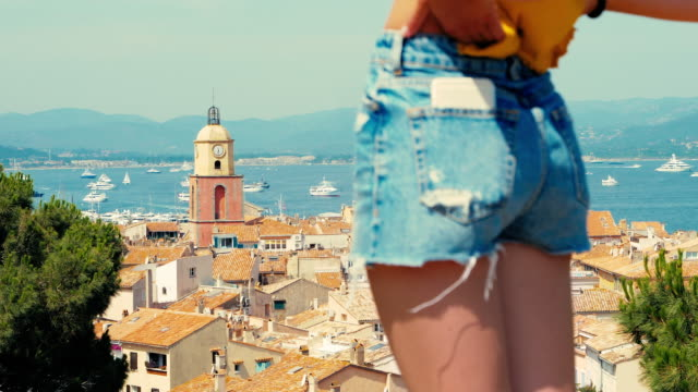 Young woman wearing denim shorts, St Tropez old town in the background