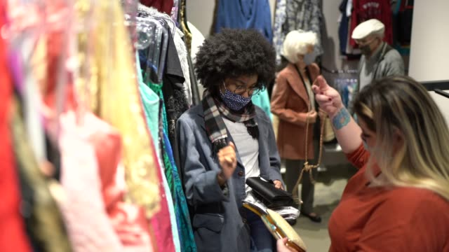 Young woman wearing face mask being helped by a saleswoman while shopping for purses in a thrift store