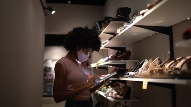 Young woman wearing face mask using digital tablet to check inventory in a thrift store