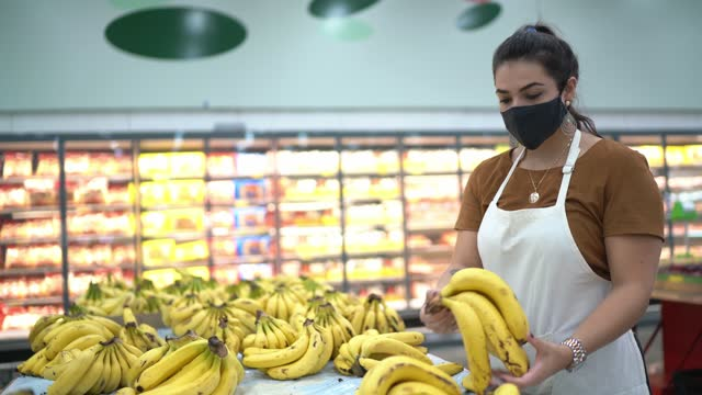 Young woman wearing face mask working in a supermarket arranging fruits