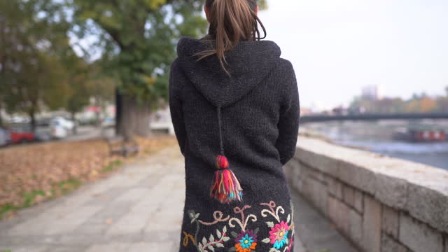 Young woman wearing long sweater walking on waterfront