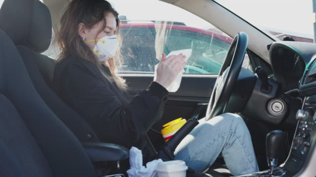 A young woman wearing protective mask cleaning hands with disinfecting wet wipes when she sitting in a car.