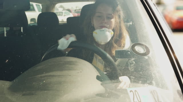 A young woman wearing protective mask cleaning steering wheel with disinfecting wet wipes when she sitting in a car.