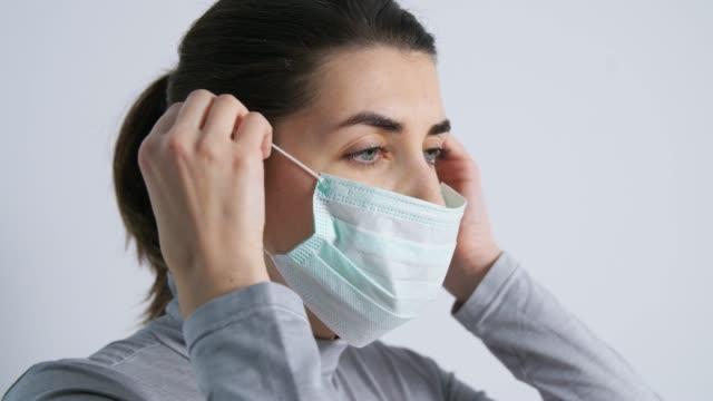 young woman wearing protective medical mask - nakładać filmów i materiałów b-roll