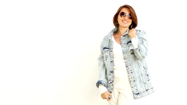 Young woman wearing sunglasses and denim jacket posing