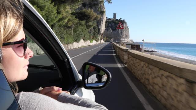 young woman wears headphones while riding in passenger seat - поколение z стоковые видео и кадры b-roll