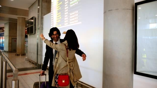 junge frau begrüßt und umarmt geschäftsmann am flughafen - welcome stock-videos und b-roll-filmmaterial