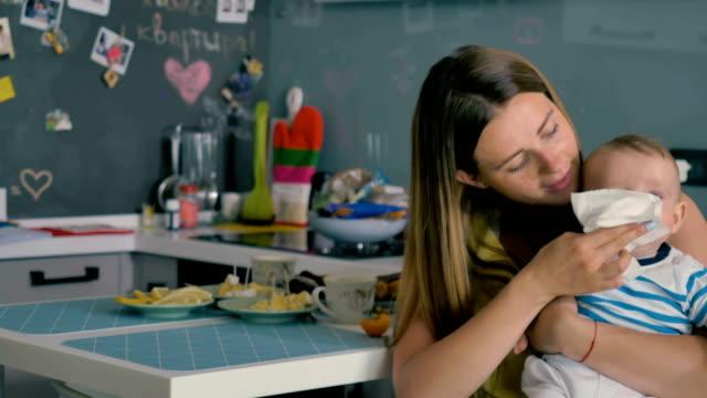 vídeos de stock, filmes e b-roll de jovem mulher limpa a boca de um bebê com um guardanapo e alimentá-lo um damasco - comida feita em casa