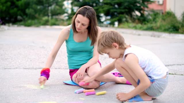 junge frau mit einem kind zieht ein kreide auf asphalt - kreide weiss stock-videos und b-roll-filmmaterial