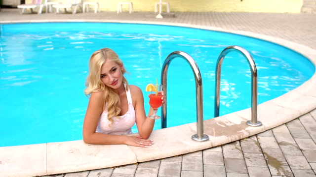 vídeos de stock e filmes b-roll de young woman with a cocktail swim in the pool. - mulher natureza flores e piscina