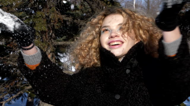 A young woman with a curly haircut in a black coat throws snow over herself