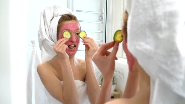 Young woman with a pink facial moisturizing mask plays with cucumber slices Young woman with a pink facial moisturizing mask plays with cucumber slices by the mirror skin care stock videos & royalty-free footage