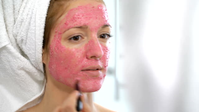 young woman with a white towel put on her face a pink moisturizing mask - facial stock videos & royalty-free footage