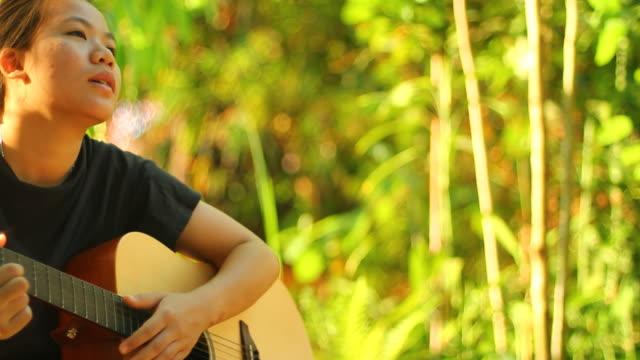 vídeos y material grabado en eventos de stock de mujer joven con guitarra accoustic - ojo morado