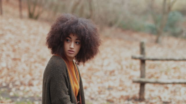 Young woman with afro hairstyle in the woods: autumn winter colors