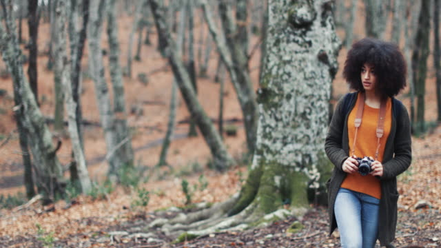 Young woman with afro hairstyle in the woods with a vintage camera