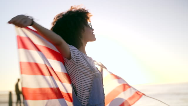 vídeos de stock e filmes b-roll de young woman with afro holding american flag - afro americano
