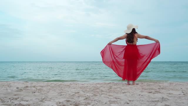 vidéos et rushes de jeune femme avec des bras écartés dans une robe rouge sur la plage de mer avec le coup de vent - bras humain