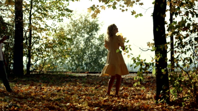 young woman with autumn leaves in hand and fall yellow maple - lingua russa video stock e b–roll