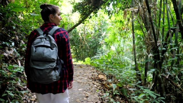 young woman with backpack on shoulders walks in thick forest - viaggiare zaino in spalla video stock e b–roll
