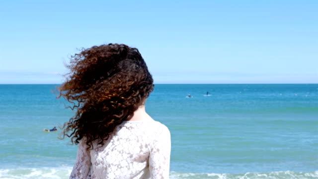vídeos de stock, filmes e b-roll de jovem mulher com gestos siga bonito cabelo cacheado me e correndo na praia - sul europeu