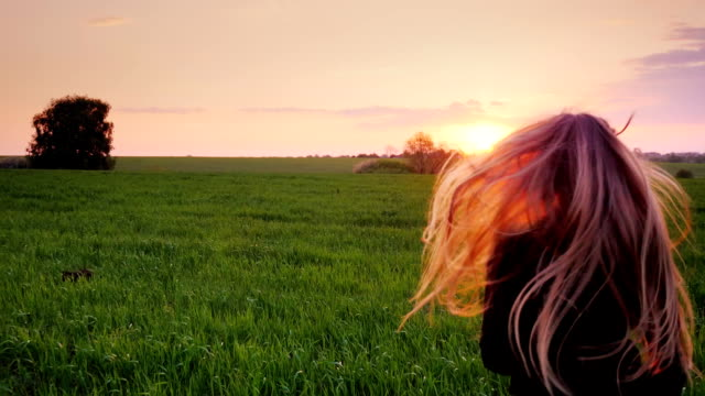 A young woman with beautiful long hair runs along the green field. Slow motion steadicam video video