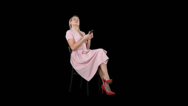 ung kvinna med blont hår sitter på en stol läsning, textning på mobiltelefon, alfakanal - endast unga kvinnor bildbanksvideor och videomaterial från bakom kulisserna