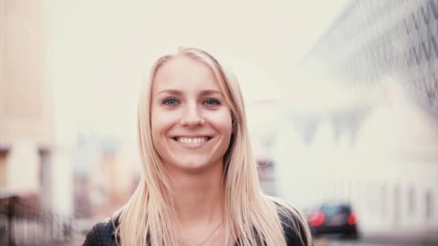 vídeos de stock, filmes e b-roll de jovem mulher com cabelo loiro, olhando para a câmera e sorrindo. retrato de uma menina bonita na cidade desfocar o fundo - camera