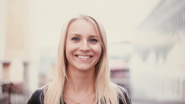 vídeos de stock, filmes e b-roll de jovem mulher com cabelo longo loiro olhando para a câmera e sorrindo. retrato de uma rapariga atraente na cidade de desfocar o fundo - camera
