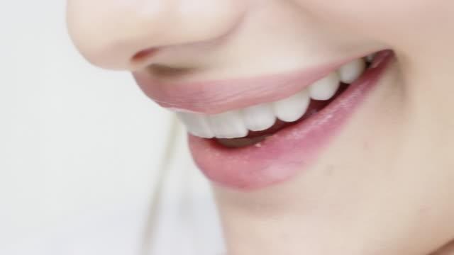 junge frau mit blauen augen, die ihre glänzenden lippen beißen - lippen stock-videos und b-roll-filmmaterial